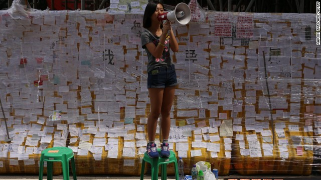 """A student protester speaks into a microphone in front of a """"democracy wall"""" filled with notes supporting the pro-democracy protest. The notes are protected from the rain with plastic wrap."""