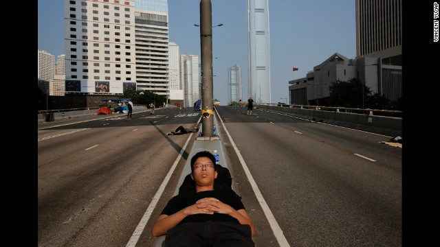 A pro-democracy protester sleeps on a street in the occupied area surrounding the government complex in Hong Kong on Wednesday, October 8.
