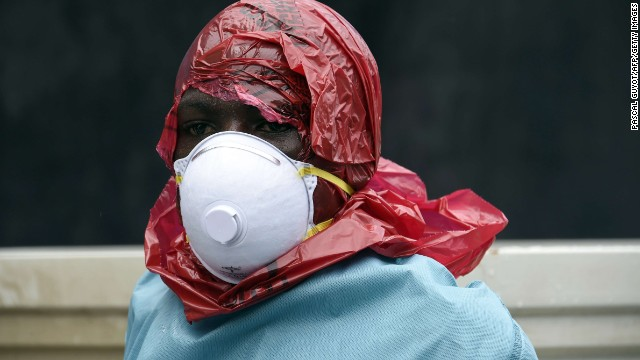 Most people in Ebola-affected areas do not have access to protective suits. Red Cross volunteers have improvised their protective wear and cover their heads with red plastic bags. They cut a hole in the bag to see and breathe.
