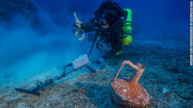 "After spending the last month at the historic wreck site, the <a href='http://www.whoi.edu/news-release/antikythera-finds' target='_blank'>Woods Hole Oceanographic Institute</a> (WHOI) announced that an international team of archaeologists had recovered new items from the Antikythera wreck. Pictured, Greek technical diver Alexandros Sotiriou discovers an intact ""lagynos"" ceramic table jug and a bronze rigging ring. The new items have indicated the wreck site is much bigger than previously believed, scattered across 300 meters of seafloor."