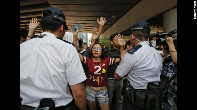 Protesters raise their hands behind police officers after people tried to remove the metal barricades that protesters set up to block off main roads near the city's financial district on October 13.