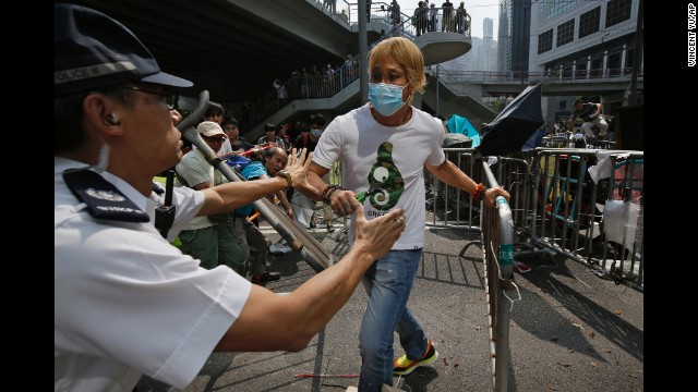 A police officer tries to stop a man from removing metal barricades set up by protesters on October 13.