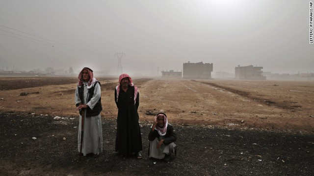 Syrian Kurds from Kobani stand outside the grounds of a refugee camp in Suruc on Saturday, October 11.