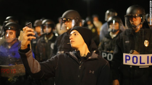 A protester takes a selfie in front of a police line during a demonstration outside the police department in Ferguson, Missouri, on Friday, October 10. Emotions have run high in the St. Louis suburb since Michael Brown, an unarmed black teenager, was fatally shot by Darren Wilson, a white police officer, in August. Protests <a href='http://www.cnn.com/2014/11/24/justice/gallery/ferguson-reaction/index.html'>intensified in November</a> after a grand jury decided not to indict Wilson.