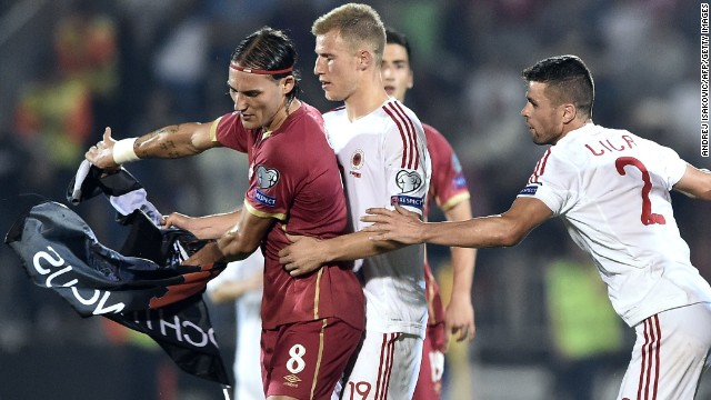 Nemanja Gudelj (L) scuffles with midfielder Albania's midfielder Bekim Balaj (C) and defender Andi Lila (R) over a flag with Albanian national symbols.