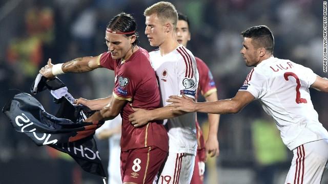 Nemanja Gudelj (L) scuffles with midfielder Albania's midfielder Bekim Balaj (C) and defender Andi Lila (R) over a flag with Albanian national symbols.