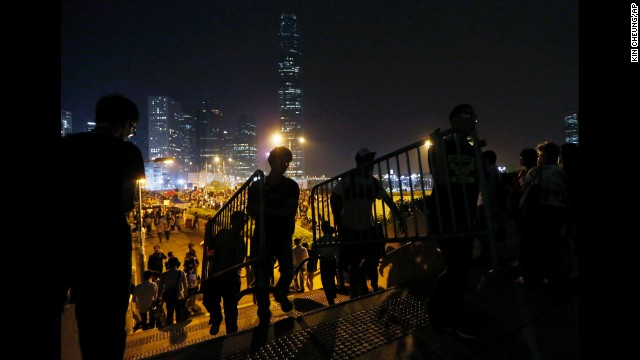 Protesters move barriers as others block a main road in Hong Kong with metal and plastic safety barriers on October 15.
