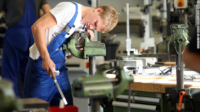 The country's unique apprenticeship scheme has played a key role in nurturing Germany's manufacturing success, with school leavers spending around 2-3 years training with companies. A trainee, pictured, files a piece of metal at a Siemens training center in Berlin.