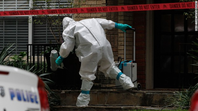 A man dressed in protective clothing treats the front porch of a Dallas apartment where one of the infected nurses resides on Sunday, October 12.