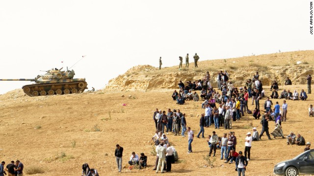 MURSITPINAR, TURKEY: Kurdish people and Turkish soldiers watch fighting in the Syrian town of Kobani from a hilltop near the Turkish-Syrian border. The strategic border town of Kobani has been beseiged by ISIS militants since mid-September forcing more than 200,000 people to flee into Turkey. Photo by CNN's Jose Armijo. Follow Jose (@josecnn) and other CNNers along on Instagram at instagram.com/cnn.