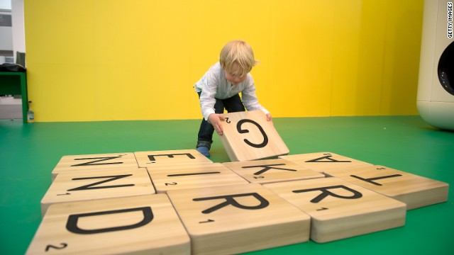"Children play with a giant scrabble set as part of Carsten Holler's installation ""Gartenkinder"", in which he the Gagosian Gallery's stand at Frieze was transformed into a children's playground."