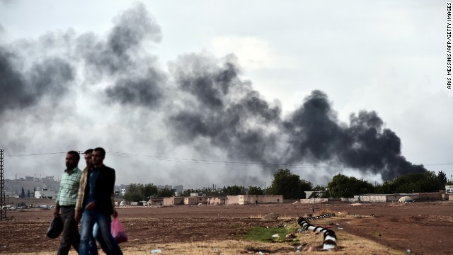Kurdish men walk near the Turkish-Syrian border as smoke rises from the Syrian town of Kobani, as seen from the southeastern village of Mursitpinar, Turkey, on October 16.