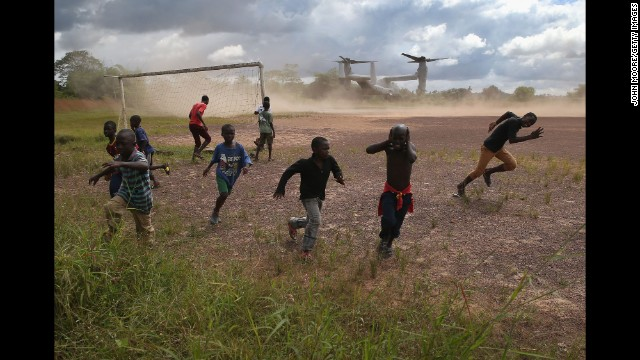 Boys run from blowing dust as a U.S. military aircraft leaves the construction site of an Ebola treatment center in Tubmanburg, Liberia, on October 15. Health officials say the Ebola outbreak in West Africa is the deadliest ever. More than 4,000 people have died there, according to the World Health Organization.