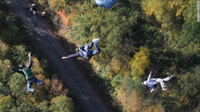 These experienced jumpers show off their skills in a three-way BASE jump at Bridge Day in 2011.