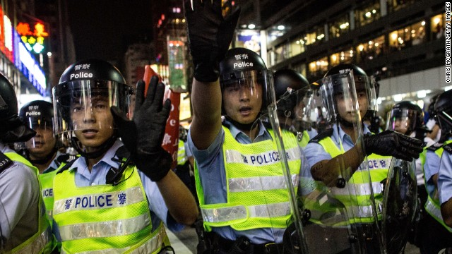 Police officers yell at pro-democracy protesters as they push forward in an attempt to clear a street on Saturday, October 18.