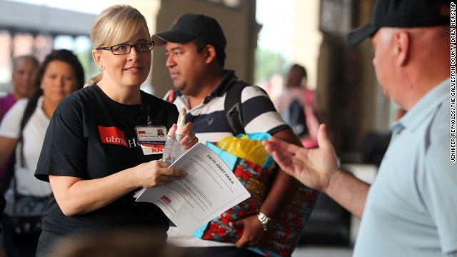 Christine Wade, a registered nurse at the University of Texas Medical Branch, greets Carnival Magic passengers disembarking in Galveston, Texas, on Sunday, October 19. Nurses met passengers with Ebola virus fact sheets and to answer any questions. A Dallas health care worker was in voluntary isolation, although she had shown no signs of the disease, in her cabin aboard the cruise ship because of her potential contact with the Ebola virus.