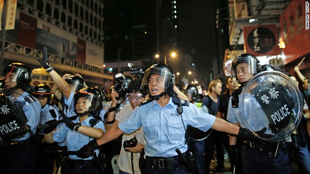 Riot police advance on a pro-democracy protest encampment early Sunday, October 19.