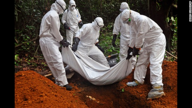 Health workers bury the body of a woman who is suspected of having died of the Ebola virus on the outskirts of Monrovia, Liberia, on Monday, October 20.