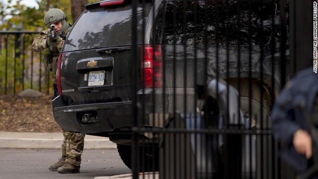 A heavily armed officer takes position at the gate of 24 Sussex Drive, the official residence of Canadian Prime Minister Stephen Harper. Harper was evacuated from the Parliament building and is safe, his press secretary tweeted.