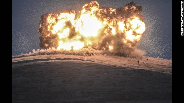 ISIS militants stand near the site of an airstrike near the Turkey-Syria border on Thursday, October 23.