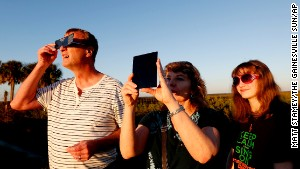 Andy, Cathy and Jessica Howell look at a partial eclipse of the sun on Thursday, Oct. 23, 2014 in Gainesville, Fla. (AP Photo/The Gainesville Sun, Matt Stamey)