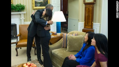 President Barack Obama hugs Ebola survivor Nina Pham in the Oval Office of the White House in Washington, Friday, Oct. 24, 2014, in Washington. Pham, the first nurse diagnosed with Ebola after treating an infected man at a Dallas hospital is free of the virus. The 26-year-old Pham arrived last week at the NIH Clinical Center. She had been flown there from Texas Health Presbyterian Hospital Dallas. Pham's mother Diana, center, and sister Cathy watch. (AP Photo/Evan Vucci)
