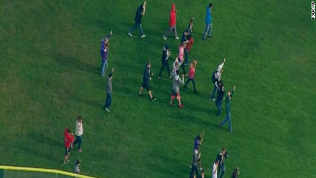 Students walk across a field after reports of shots being fired at the school.