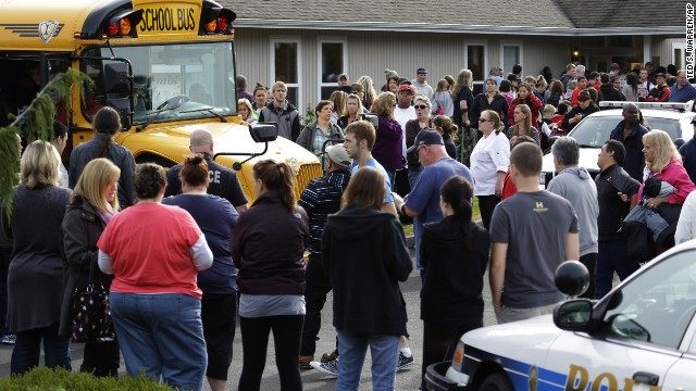 Parents crowd around buses as students arrive at the church.