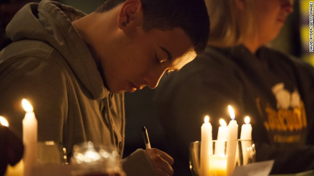Students from Marysville-Pilchuck High School write messages and prayers during a vigil Friday, October 24, at a church in Marysville, Washington. Earlier in the day, <a href='http://www.cnn.com/2014/10/27/us/washington-school-shooting/index.html'>a student shot five people at the school</a> before he committed suicide, law enforcement officials told CNN.