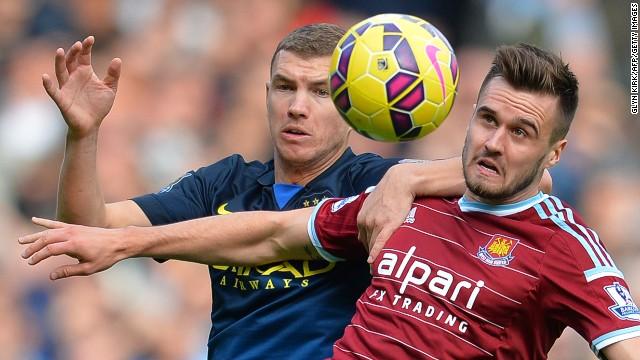 Manchester City's Edin Dzeko (L) challenges West Ham midfielder Carl Jenkinson during Saturday's game.