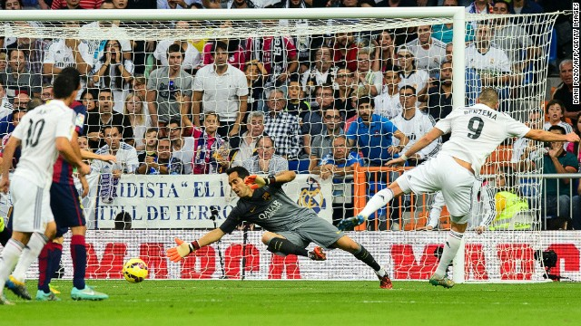 Karim Benzema (right) slides his shot past Claudio Bravo to score Real Madrid's third goal against Barcelona in Saturday's El Clasico.
