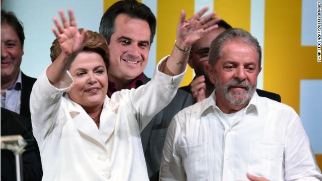 Re-elected Brazilian President Dilma Rousseff (L) waves next to former Brazilian President Luiz Inacio Lula Da Silva, following her win, in Brasilia on October 26, 2014.