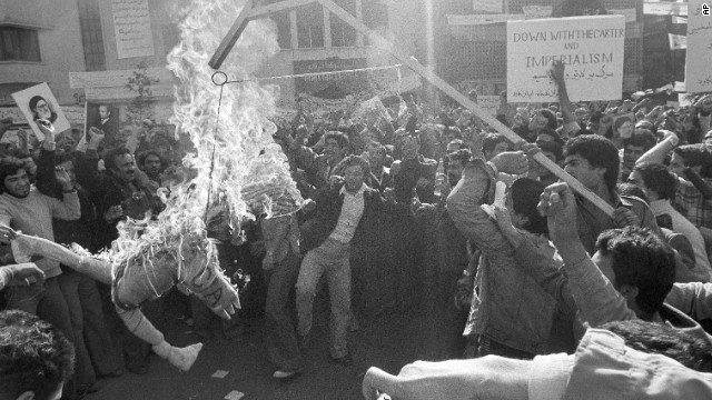 """Demonstrators burn an effigy of Uncle Sam outside the U.S. Embassy in Tehran on November 13, 1979. They had gathered to show support for the Iranian militants who took over the embassy. The effigy was branded with """"CIA"""" on its arm."""