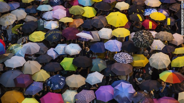 People open umbrellas at the main protest site in Hong Kong on Tuesday, October 28. The umbrella has become the defining image of the protest movement, used to shield protesters from tear gas and the elements.