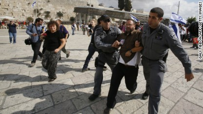 Israeli police detain right-wing activist Noam Federman after he tried to enter the Temple Mount the most sacred spot for Jews because it once housed two Jewish temples, also know as the Al-Aqsa mosque compound, Islam's third holiest site in the old city of Jerusalem, on October 30, 2014 after Israeli authorities temporarily closed the compound. Israel's closure of the flashpoint Al-Aqsa mosque compound to all visitors following the shooting of a Jewish hardliner is tantamount to a