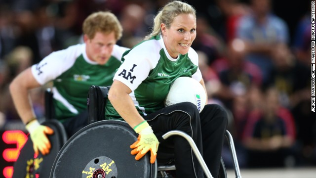 In September 2014, Phillips and her husband took part in a wheelchair rugby exhibition match during the Invictus Games for war veterans organized by her cousin Prince Harry (pictured behind).