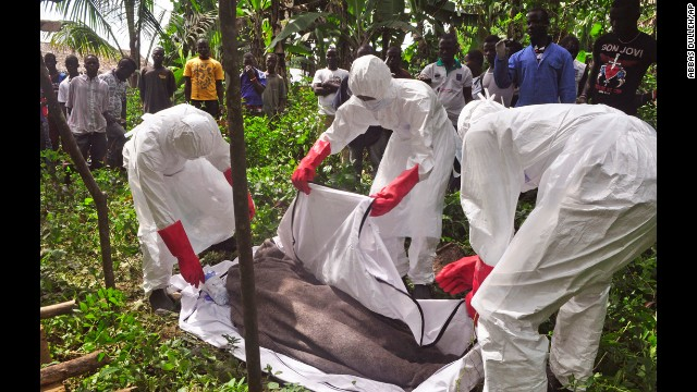 Health workers in Monrovia, Liberia, cover the body of a man suspected of dying from the Ebola virus on Friday, October 31.