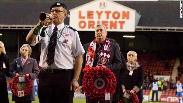 A man wears a Hearts scarf and holds a wreath to represent the Scottish club during a remembrance ceremony at Orient's stadium in east London.