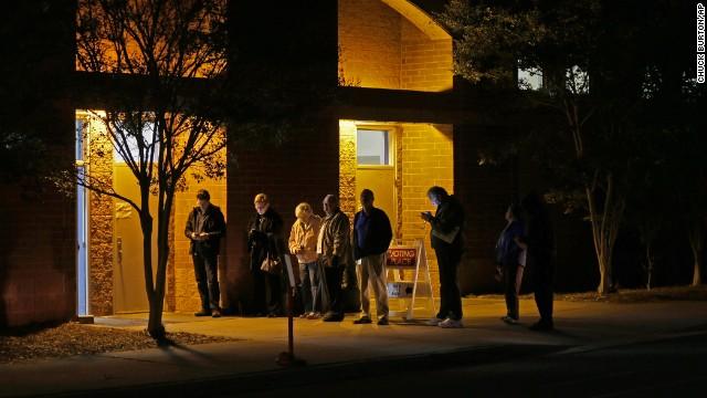 A handful of people wait in line before polls open November 4 at Elizabeth Lane Elementary School in Matthews.