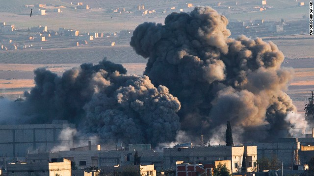 A bomb (upper left) falls on an ISIS position in Kobani, Syria. during an airstrike by the U.S.-led coalition on Saturday, November 8. ISIS militants and Syrian Kurdish fighters have been battling for control of the city near the Turkish border, and the United States and several Arab nations have been bombing ISIS targets to take out the group's ability to command, train and resupply its fighters.
