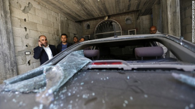 Fayez Abu Eitta, left, a Fatah leader in Gaza, speaks on the phone as he inspects the damage to his car.