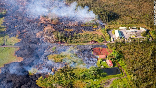 Lava flows near a residential structure in Pahoa, Hawaii, on Monday, November 10. The lava flow from the Kilauea Volcano is advancing on the community of about 950 people on Hawaii's Big Island and claimed its first home in the town, which has been watching the slow-moving flow approach for months.