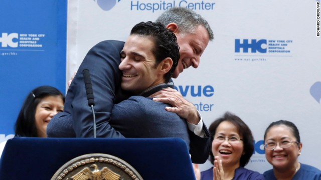 The first Ebola patient in New York City, Dr. Craig Spencer, gets a hug from New York Mayor Bill de Blasio, left, during a news conference on Tuesday, November 11. Now free of Ebola, Spencer was released 19 days after being diagnosed with the virus. The physician had been working with Doctors Without Borders, treating patients in Guinea.