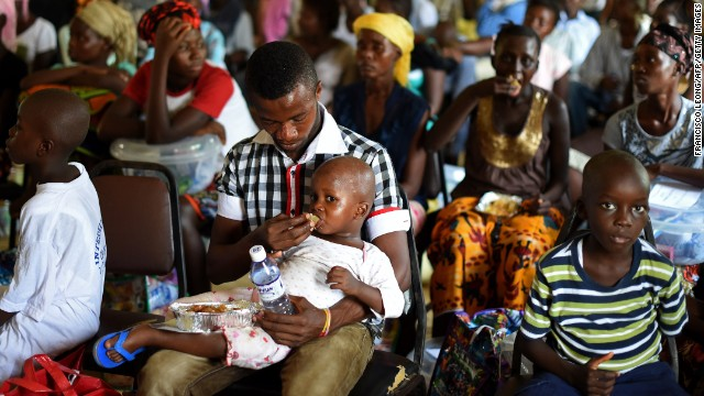 A child who survived the Ebola virus is fed by another survivor at a treatment center on the outskirts of Freetown, Sierra Leone, during a Tuesday, November 11, ceremony at which 63 survivors at the center were discharged.