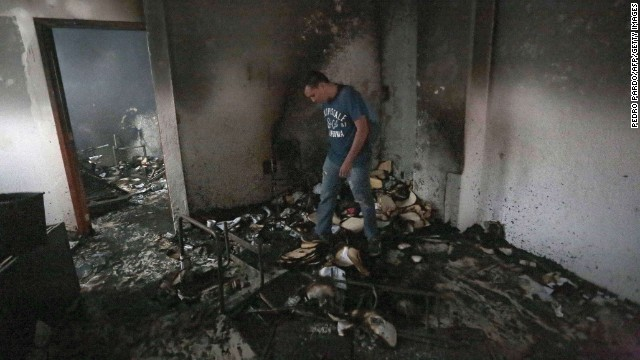 A man walks through rubble after demonstrators set the Institutional Revolutionary Party's headquarters ablaze in Chilpancingo, Guerrero state, Mexico, on November 11.