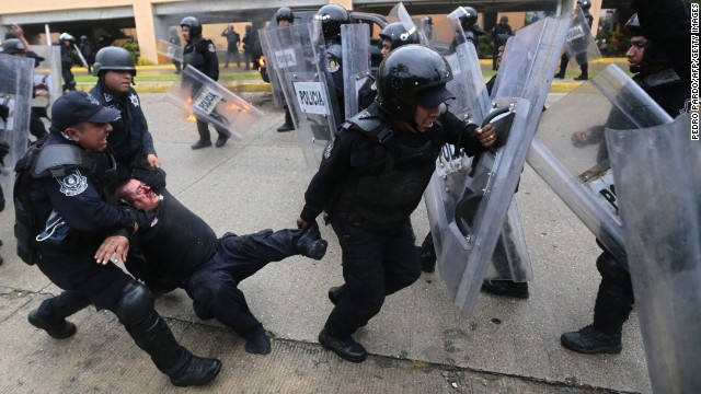 A wounded riot police officer is rescued from violent demonstrators on November 10.