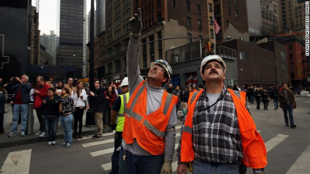 Construction workers look up at the scaffold.