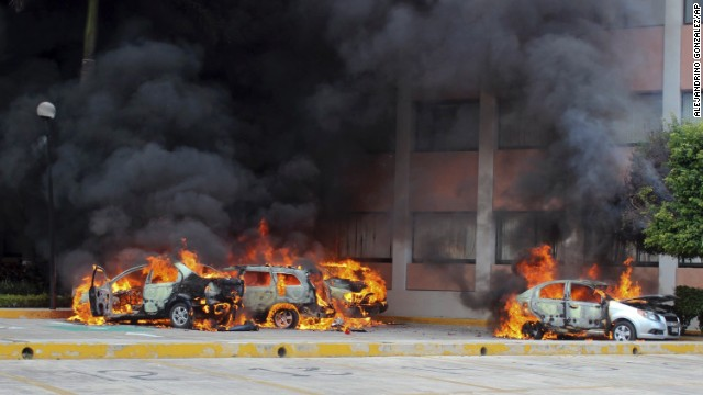 "Cars burn in front of the state Congress building in Chilpancingo on Wednesday, November 12. <a href='http://www.cnn.com/2014/11/04/world/americas/mexico-missing-students/index.html'>Authorities have arrested Iguala Mayor Jose Luis Abarca</a>, called the ""probable mastermind"" in the mass abduction, and his wife, Maria de los Angeles Pineda."