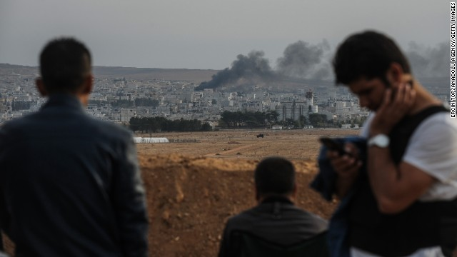 People in Suruc watch smoke rise near the Syrian border during clashes between ISIS members and armed groups on Thursday, November 13.
