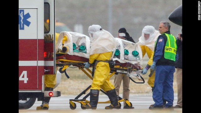 Health workers in protective suits transport Dr. Martin Salia from a jet that brought him from Sierra Leone to a waiting ambulance in Omaha, Nebraska, on Saturday, November 15. Salia died early Monday, November 17, after being brought to the United States for treatment of Ebola.